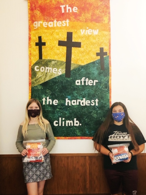 "Image is of two young women in front of a brightly colored banner with the image of three crosses on a field of hills. Text says ""The greatest view comes after the hardest climb."" The women are holding ziploc bags of cloth face masks and each is wearing a mask of her own."