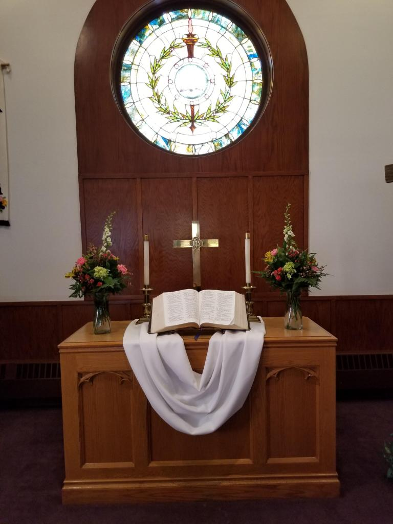 A church alter sits below a circular stained glass window. The window is lit brilliantly from behind with its image of a staff encircled by olive branches very visible. The alter below is decorated with two spring bouqets with bright green, pink, yellow and white flowers. On the alter itself sits two candles on either side of an open Bible and golden cross. A white sash lies beneath all of these things on the table top.