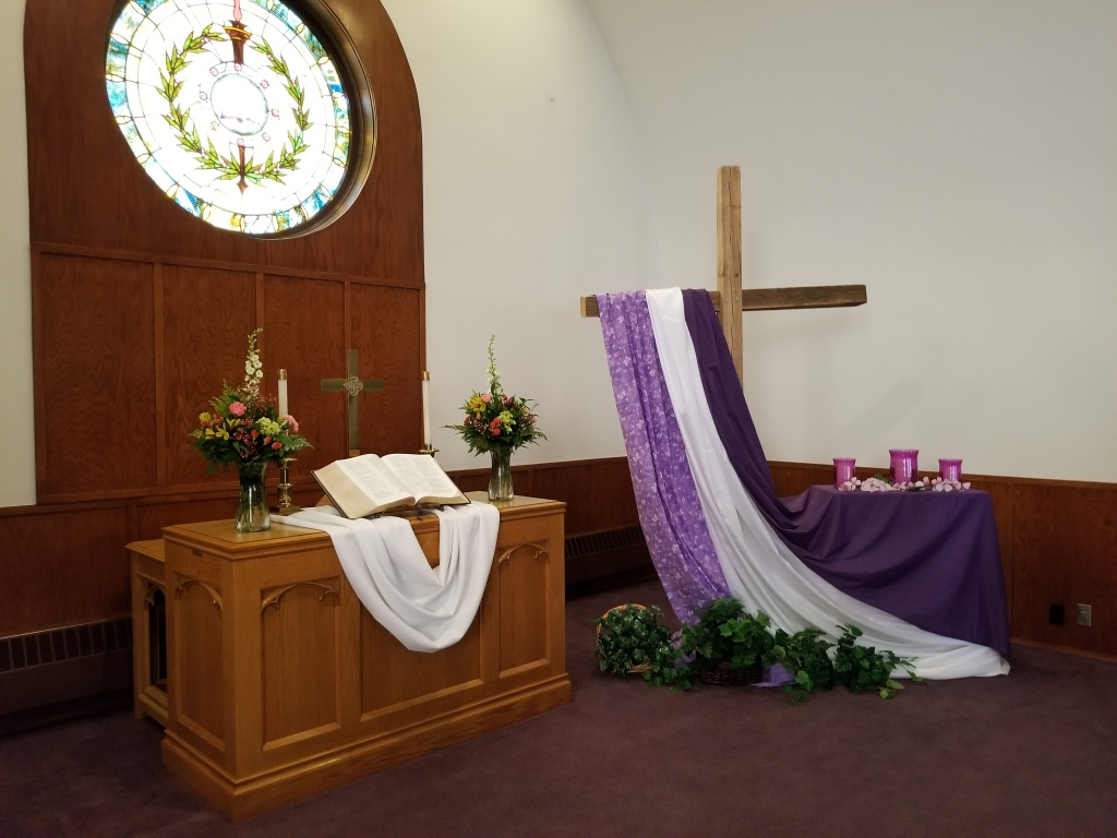 An image of the front of a church, with a stained glass window high in the left corner of the window. The stained glass window is lit from behind and the staff and olive branches are clearly visible in it. The alter with flowers, open Bible, candles, white sash, and cross are beneath the window on the lower left corner of the image. On the right half of the image is a large wooden cross, standing taller than the average person. Vibrant purple, violent, and white sashes are draped on the left arm of the cross, running to the floor. A small table sits behind to the right of the cross with another purple sash and some purple items of unknown matter are on top of it.